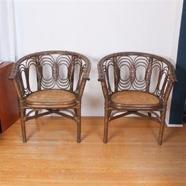 Pair of Mid Century Cane and Bamboo Club Chairs: A pair of Mid Century cane and bamboo club chairs. Each features a curved bamboo back with layered rattan ovals and wrapped details, a caned seat, and bamboo legs connected by an x stretcher. Items are not marked.