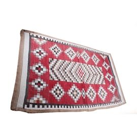 Antique Handwoven Native American Style Flatweave Rug: An antique handwoven Native American style flatweave area rug. This rug features a center red diamond medallion flanked by a chevron pattern in gradient brown hues. Surrounding the center design is a geometric diamond pattern against a red field. The rug has a beige and white trim and is not labeled.
