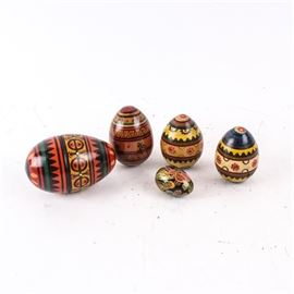 Ukranian Hand Painted Wood Eggs: A collection of Ukranian hand painted wood eggs in various sizes. The medium eggs feature alternating floral and geometric designs and the smaller egg features an intricate floral motif. The largest is a nesting egg with a smaller matching egg to the interior. Each features a lacquered finish.