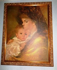 Beautiful oil of a mother and her child with a fancy wood frame finished in gold.