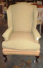 Comfortable yellow plaid wing chair with wooden legs.