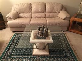 Ivory leather sofa, contemporary glass top coffee table and area rug