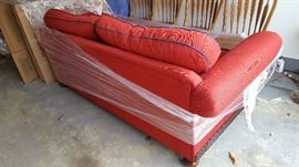red couch, navy blue piping on cushions, wood feet and detailing
