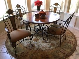 Wood, wrought iron dining set with 4 upholstered seat arm chairs, also round rug with fringe