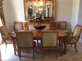 Carved wood dining table with inlays, extension leaf and 8 chairs with upholstered backs and seats (2 are armchairs), also matching buffet behind on wall (see other photos of that and table leg details)
