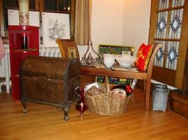Contemporary trunk, paper mache mask of a Chinese woman, Turkish coffee set, Anchor Hocking Rachel fruit bowl set, pencil drawings from Saudi Arabia, Chinese red painted corner bookcase