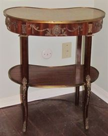 19th Century French Kingwood ormolu mounted kidney shaped side table with a center lower tier. The  parquetry top and lower tier is enclosed in a cast bezel.  The center of the apron has an escutcheon with a wonderful detailed foliate. There are similar mouldings  on the sides. The table stands on thin, elegant cabriole legs. The knees have a very elaborate Rococo casting with acanthus leaves and flowers with continue beading down the front and finish in very elegant sabots.