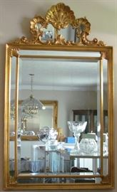 """Carvers' Guild Shell Chippendale Bevel Mirror with Gold Leaf Finish in an 18th Century looking glass   Rococo style, the Shell Chippendale with voluting C scrolls, acanthus leaf, magnificently crested by a classical shell. The hand laid gold leaf finish glows with antique patina. The mirror measures 32""""W X 53""""H  with a beveled mirror. The production time for this mirror was approximately 6-8 weeks."""