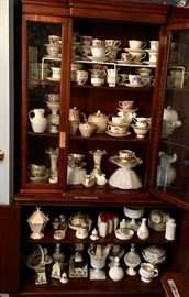 Tall solid wood china cabinet filled with glassware and china collections.