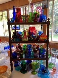 Display of a variety of vintage and antique, uniquely shaped glass bottles, cruets, and other glassware in all the colors of the rainbow!