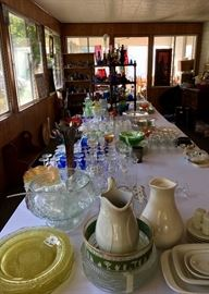 A room long view displaying the variety of stoneware, punch bowl sets and cups, specialty etched glassware, glass, glass, glass..including a bottle collection.