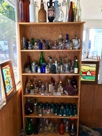 Part of the bottle collection surrounded by stained glass pictures.