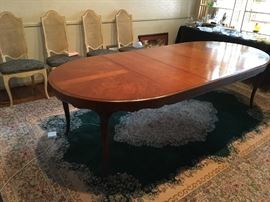Henredon solid cherry dining table, oval with three leaves atop vintage Karastan Green Kirman rug.