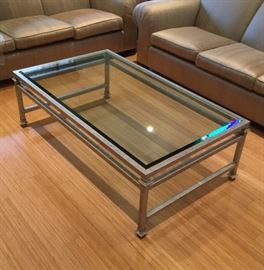"""Steel & Glass Coffee Table •Silver and beveled glass coffee table. •Measures 58"""" L by 34"""" W by 18.5"""" H"""