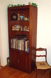 Lighted Bookcase containing Hummels, 78 records, Roseville vase and etc.
