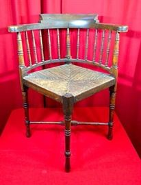 Antique corner chair with turned legs and wicker seat