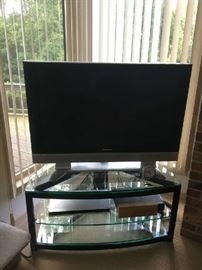 "Glass & base metal  1/2 moon  TV stand 44""long 19""h, 19""w with a Panasonic 42"" HDTV Model no. TH42PX50U"