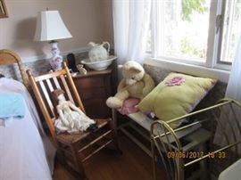 The oak wash stand has 2 drawers and 2 door to open the cabinet. The Maple rocking chair has a woven seat. The early doll is cloth with hand painted face. The pine bench and the towel rack on the right. The Teddy bear and embroidered pillow sit on the bench.