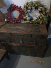 Two Christmas wreaths sit on a flat top trunk