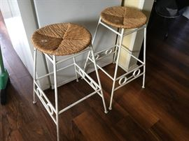 two wrought iron bar stools with rattan seats