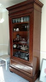 This china cabinet/display case breaks down in 3 easy to move pieces. It also has a hidden drawer in the foot molding under the obvious lower drawer. See next picture. This is a beautiful piece of older furniture