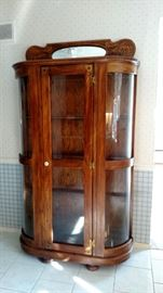 This oak case has glass shelves and is lighted