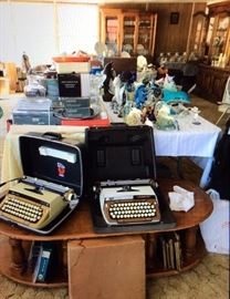 Large collection of Dolphin figurines, two vintage typewriters, vintage desks, antique library table