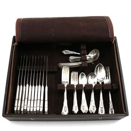 "Wallace ""Rosepoint"" Sterling Silver Flatware and Case: A set of Wallace sterling silver dinner flatware in the Rose Point pattern, 1934-present. A leather like zippered and snap fastener case with tarnish proof felt lining is included with the set. Based on the fine, delicate floral schemes found in needlepoint and lace, Rose Point is designed with scrolls, roses and pierced detailing. This set includes the following: ten dinner knives with stainless blades, eleven dinner forks, ten salad forks, ten teaspoons, eight soup spoons, four serving spoons, one serving fork, one ladle, eight butter knives, one master sugar, and twelve demitasse spoons. A total of seventy-five pieces. Total approximate weight of the flatware excluding the dinner knives: 71.860ozt."