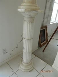 Solid White marble fluted column on which marble lamp sits.