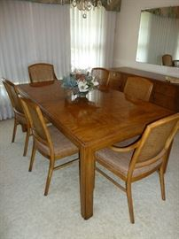 Solid wood Drexel Heritage dining table.  Has six chairs with caned backs and cushion seats.
