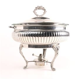 "Chafing Dish and Pyrex Insert: A chafing dish and Pyrex insert. This set includes a silver tone chafing dish with a frame, support ring, lid, and fuel container as well as a Pyrex brand insert dish with two handles. The dish is marked ""Pyrex"" and ""3 QT."" to the underside."
