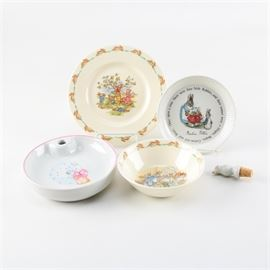 "Porcelain Tableware and Wine Stopper Featuring Wedgwood: An assortment of porcelain tableware featuring two plates, two bowls, and a wine stopper. The plates include a Royal Doulton Bunnykins Albion shape bone china plate with rabbits picking apples and a Wedgwood Peter Rabbit porcelain plate with a Beatrix Potter quote around the rim. Also included are a Bunnykins bowl with rabbits in a bathtub and Pillivuyt child's cereal bowl with a rabbit blowing on a dandelion. The Bunnykins pieces are marked ""Royal Doulton"" while the Peter Rabbit plate is marked ""Wedgwood of Etruria & Barlaston"" to the underside. The cereal bowl is marked ""Pillivuyt France"" to the underside. The wine stopper features a simplistic bird figure attached to a cork. There are no visible maker's mark to the piece."