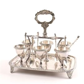 "English Silver Plate Egg Cruet Set with Sterling Spoons: An ornate silver plate egg cruet set. This features six pedestal egg cups with gadrooned rims that side on a rectangular tray with scrolling feet, and an elaborate foliate handle. It is marked with an unidentified maker's mark of ""WS"", a clover, feathers, ""EP"" and ""A1"". It is presented with six sterling silver spoons that are marked ""Prata 950"". The total approximate weight of the spoons is 2.495 ozt."