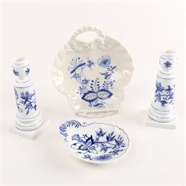 "Meissen ""Blue Onion"" Porcelain Tableware: A collection of tableware and candlesticks in the Blue Onion pattern. There are three Meissen examples from the twentieth century in the popular underglaze blue decoration. This 1750's pattern was derived from Chinese imagery but named in a manner that Germans and other Europeans could relate to. The pattern has been in production since that period by many firms including a piece in this collection which is as of yet unidentified. The other examples have the underglaze blue crossed swords marks for the Meissen factory."