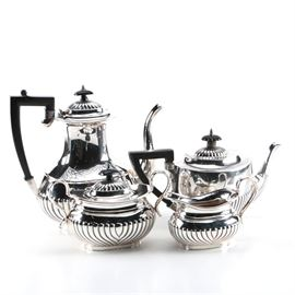 "English Silver Plate Tea and Coffee Service: An English silver plate tea and coffee service. This includes a teapot, a coffee pot, a lidded sugar bowl, and a cream pitcher, each featuring oval bodies ornamented with bat-wing fluting. The coffee pot is marked with various marked underneath including ""A1"", ""RR"", ""warranted hard soldered"", ""1203"" and a pictorial maker's mark of an anchor, while the other pieces are marked ""Made in England"" and ""E.P on Copper""."