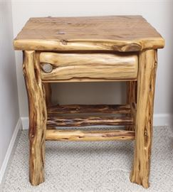 Mountain Cedar Side Table: A mountain cedar side table. This rustic table is formed from cedar branches with a single shelf to the base. The branches are in their natural form to the base and have been planed to form the top. It has a natural finish.