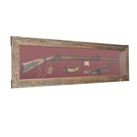 Fifty Caliber Mountain Man Flint Lock in Case with Other Items: A framed shadow box with assorted frontier items. Included is a 50 caliber flint lock mountain man weapon, a powder horn, small leather pouch and a peace pipe. These items are all mounted on a red background framed with a barn board frame. There is an informational tag to the middle of the case.