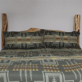 Pendleton King Size Bedding: A Pendleton wool bedspread and pair of pillow shams. This king sized spread is woven in tones of forest green, muted orange and tan. The pieces feature a Northwestern Native American geometric design manufactured at the Pendleton woolen factory in Oregon state.