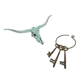 Southwestern Decorative Metal Items: An assortment of metal decorative items. Including a heavy brass ring with three old fashioned keys and a heavy metal longhorn steer skull with a green distressed finish.