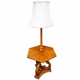 Vintage Lamp Table: A vintage lamp table. This piece features a white shade atop a wooden rod. The rod fixes to the top of a hexagon shaped table top. The top rests on three scrolled supports, atop a triangular base. The lamp powered on when tested.