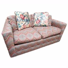 Vintage Sleeper Love Seat by Sherrill: A vintage sleeper love seat by Sherrill. This piece features upholstery in a vibrantly colored chevron pattern. It has square arms and seating for two, with a pull-out sleeper frame and mattress. Four throw pillows are included, two with matching fabric and two with a floral print. The love seat is marked beneath the seat cushions. For a coordinating piece, see item 17NAS110-001.