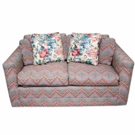 Vintage Sleeper Love Seat by Sherrill: A vintage sleeper love seat by Sherrill. This piece features upholstery in a vibrantly colored chevron pattern. It has square arms and seating for two, with a pull-out sleeper frame and mattress. Four throw pillows are included, two with matching fabric and two with a floral print. The love seat is marked beneath the seat cushions. For a coordinating piece, see item 17NAS110-002.