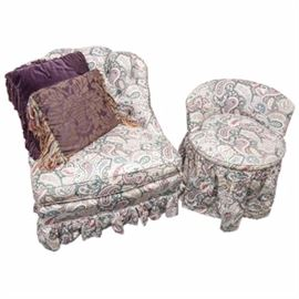 Vintage Paisley Print Chairs: A pair of vintage paisley print chairs. This pair of chairs includes a slipper style chair and a vanity chair. The slipper style chair has a scalloped crest and button-tufted back. The vanity chair has a low curved back and circular seat. Both have ruffled skirts. Two fringed accent pillows are included.