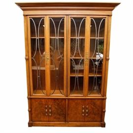 Vintage China Cabinet by Tomlinson: A vintage china cabinet by Tomlinson. This piece features a crown molding over glazed panel doors including escutcheons, pulls, lozenge and split oval shapes and enclosing shelving. The cabinet includes lower panel doors which have figured veneer and decorative pulls. The piece terminates in a plinth base.