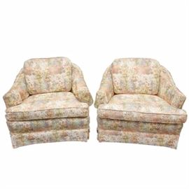 Pair of Vintage Upholstered Accent Chairs: A pair of vintage accent chairs. Each chair features a barrel back design with sloping arms, oversized cushion back and seat and box pleat skirt. The chairs are upholstered in a kaleidoscope of pastel colored flowers and are unmarked.