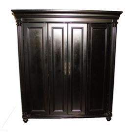 Black Wooden Computer Armoire: A black wooden computer armoire. It has crown molding to the top, above two doors, each with double panel design to the front with brass tone pulls, flanked by reeded columnar front stiles, all raised on bun feet. Inside, it has a large open section over shelving and drawers to the bottom.