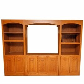 Oak-Finished Entertainment Center: An oak-finished entertainment center. This entertainment center features a rectangular top over a large center opening with recessed lighting, flanked on each side by arched openings with three display shelves. The lower half of the center features seven raised panel cabinet doors with wood pulls. The piece is unmarked.