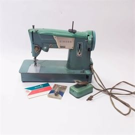 "1960s Singer ""Spartan"" Sewing Machine: A 1960's Singer Spartan sewing machine. This Singer Spartan sewing machine is model number 327K. Features include a green aluminum housing with zig/zag sewing, drop-in bobbin and foot pedal. This sewing machine from Singer was made in Great Britain. Includes original instruction manul and an extra light bulb."