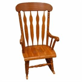 Windsor Style Rocking Chair: A Windsor style rocking chair. The wooden frame features a rectangular crest with rounded shoulders above a spindled back. The scrolled armrests are supported by spindles that attach to the contoured seat. The chair rises on four turned legs joined by a box stretcher and ending in curved runners.