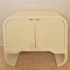 Circa 1980 Contemporary Style Textured Wood End Table: A circa 1980 contemporary style textured wood end table. This piece is cream colored with a chiseled-like texture. The top curves at the the sides, around a pair of hinged doors with shelving within. The side panels extend downward, curving inward to form two bases on each side. For coordinating pieces, see items 17CHI132-001 and 17CHI132-003.